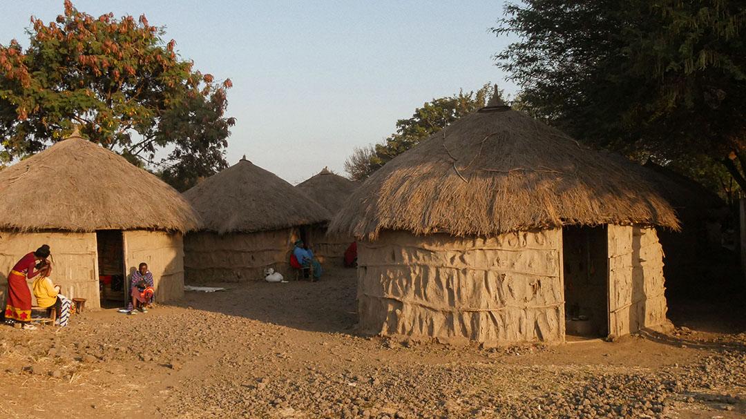 Strohhütte in Tansania Dorf braun Sonnenuntergang Frauen sitzen davor